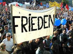 Menschenmenge mit Fahnen und Luftballons, Transparent: «Frieden».